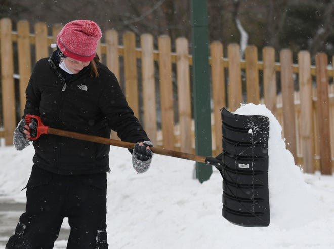 Olivia Gross, 10,  shovels fresh snow off the drive at her Lake Township home.  Tuesday, February 16, 2021.
