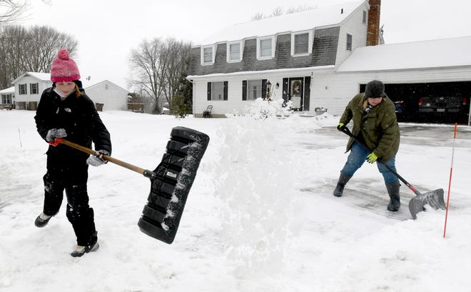 Olivia Gross, 10 and mother, Dawn Gross, shovel fresh snow off the drive of their Lake Township home.  Tuesday, February 16, 2021.