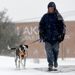 Jenny Gable of Green takes a walk with Lilly at Lake Township Park on a snowy morning Tuesday, February 16,  2021.