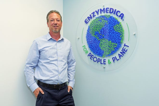 """Enzymedica CEO Scott Sensenbrenner poses in front of a logo that includes the Enzymedica motto, """"For People & Planet,"""" in a meeting room at the company's offices at 771 Commerce Drive, Venice."""