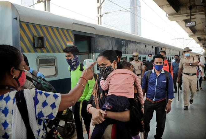 A health worker checks the temperature of a commuter at a train station in Mumbai, India, Thursday, Feb. 11, 2021. When the coronavirus pandemic took hold in India, there were fears it would sink the fragile health system of the world's second-most populous country. Infections climbed dramatically for months and at one point India looked like it might overtake the United States as the country with the highest case toll. But infections began to plummet in September, and experts aren't sure why. (AP Photo/Rajanish Kakade)