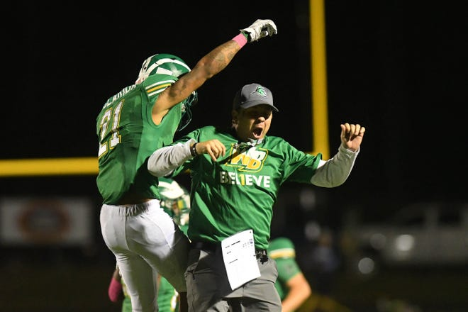 West Brunswick's De'Andre Clarida celebrates his interception with coach Brett Hickman during the Trojans' 14-7 victory over Hoggard in October 2019. It was West's first win over the Vikings since 1997.