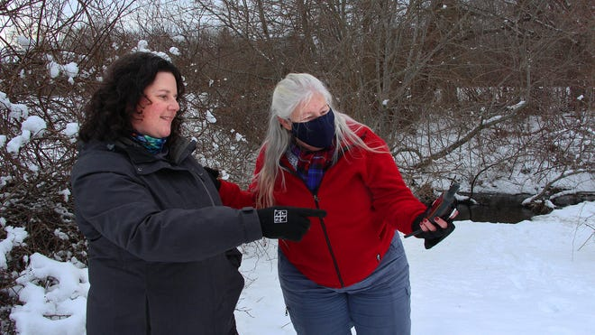 Sarah Audette (right) and Judy Widger (right) search the area for a hidden geocache in Fairhaven.