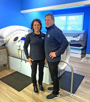 Delaware Hyperbarics co-founders Liz Gudia and Steve Caldwell pose next to a hyperbaric oxygen.