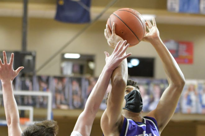 Topeka West's Trevion Alexander (20) goes in for a basket against Jack Bachelor (1) and Washburn Rural during Monday's game at Rural. Alexander got the Chargers going and scored 14 points in a key 66-46 win.