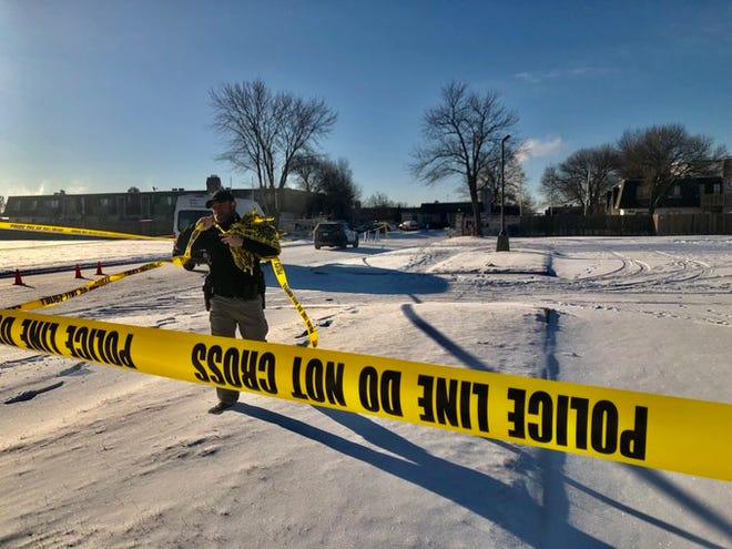A police officer removes yellow crime scene tape Tuesday morning from the scene of a homicide in south-central Topeka.