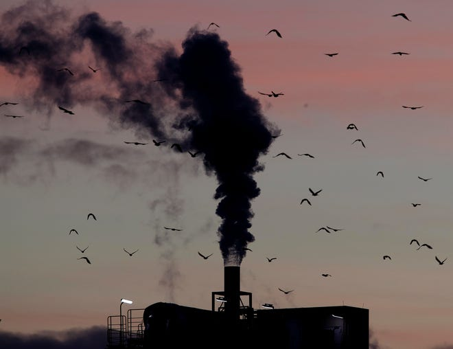 Birds fly past a smoking chimney.