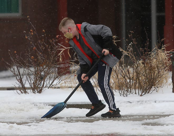 Tyler Fewkes, 13, of New Philadelphia, works on cleaning the sidewalk in front of the gazebo on the square Tuesday.