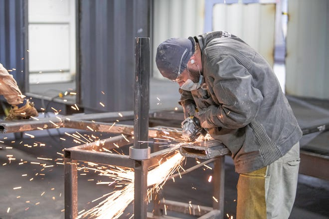 Andres Brown uses a grinder on a steel frame at indieDwell in Pueblo.