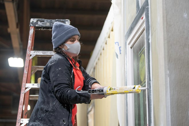 Gwennie Halbrook caulks a window of  one of the modular homes being built at indieDwell on Tuesday, Feb. 16, 2021, in Pueblo, Colo.
