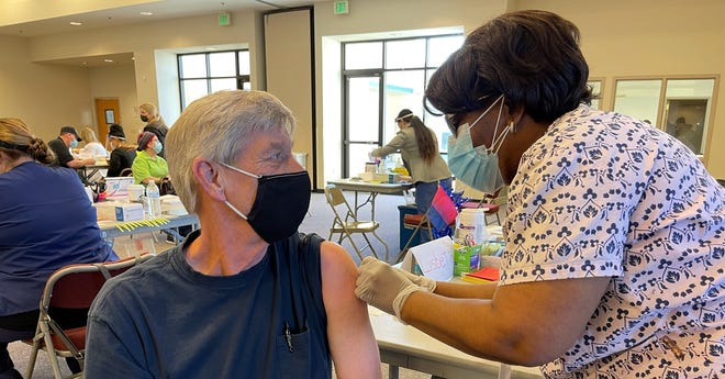 Mike Montandon, 67, of Apple Valley receives the first COVID-19 vaccine Tuesday morning at Providence St. Mary Medical Center's newly converted community clinic.