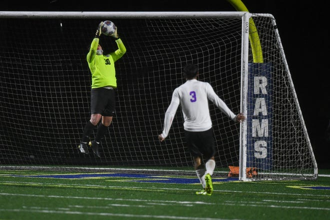North Henderson goalkeeper Edgar Soto makes a save as teammate Leonardo Dominguez (3) looks on during Monday's match at T.C. Roberson. [ANGELA WILHELM/ ASHEVILLE CITIZEN-TIMES]
