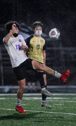 North Henderson's Rubisel Sanchez (12) and T.C. Roberson's Noah Ballard fight for the ball  in the pouring rain on Monday night at Roberson. [ANGELA WILHELM/ ASHEVILLE CITIZEN-TIMES]