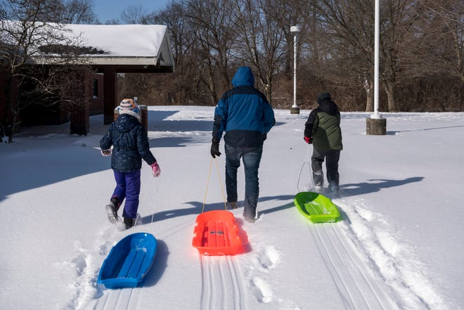 Ten-year-old Sarah Corbett, left and 8-year-old David Corbett, right, trek through the snow with their father Jonathan Corbett to go sledding at Helfrich Hills Golf Course in Evansville, Ind., Tuesday, Feb. 16, 2021. Jonathan said the last time they used their sleds was in January 2018, when the Evansville-area received a little over 7 inches of snow.