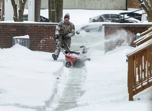 Marty Thomas snow blows sidewalks to apartments on Tuesday, Feb. 16, 2021, in Broad Ripple Village in Indianapolis. The winter storm brought up to 6 to 10 inches of snow across Indianapolis.