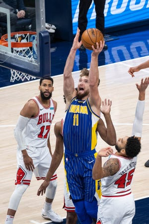 Feb 15, 2021; Indianapolis, Indiana, USA;  Indiana Pacers forward Domantas Sabonis (11) shoots the ball while Chicago Bulls guard Denzel Valentine (45) defends in the third quarter at Bankers Life Fieldhouse.