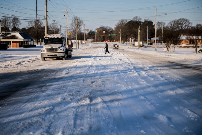 A man crosses North Parkway at 8:05am on Tuesday, Feb 16, 2021 in Jackson, Tenn.