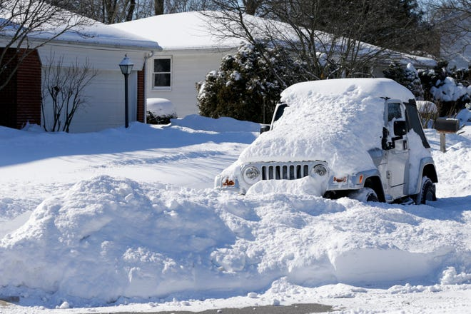 A jeep sits covered in snow, Tuesday, Feb. 16, 2021 in West Lafayette.