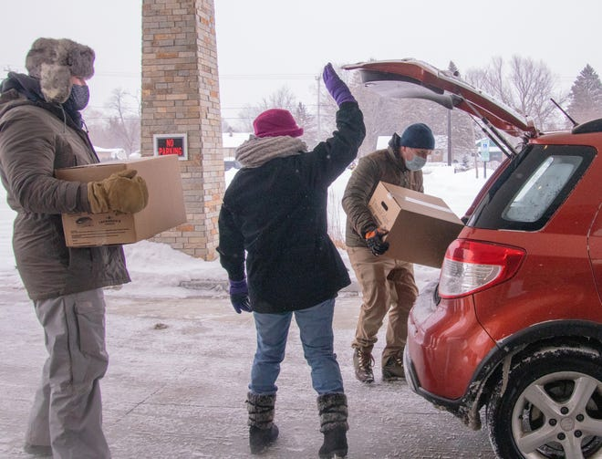 Volunteers with Layton Avenue Baptist Church in Greenfield load food boxes into a vehicle during a food giveaway at the church Saturday, Feb. 13. Loading the vehicle are (from left) Glenn Gaskill III, Sheila Carignan and Mark Moulis. The effort was part of the USDA's Farmers to Families program, a federal initiative put in place to help feed those in need during the pandemic.