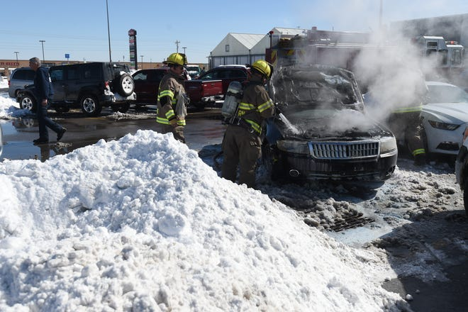Mountain Home firefighters extinguish a car fire at Walmart on Tuesday. The inclement weather impacts how law enforcement officers, firefighters and medical personnel respond during emergencies.
