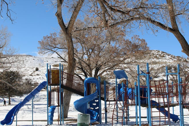 A fresh layer of snow from a Valentines' weekend storm that led to energy cost price spikes covers the playground at Kiwanis Park in Farmington on Feb. 16, 2021. Some on the Public Regulation Commission want to see what else was left behind, such as price hikes for utility customers.