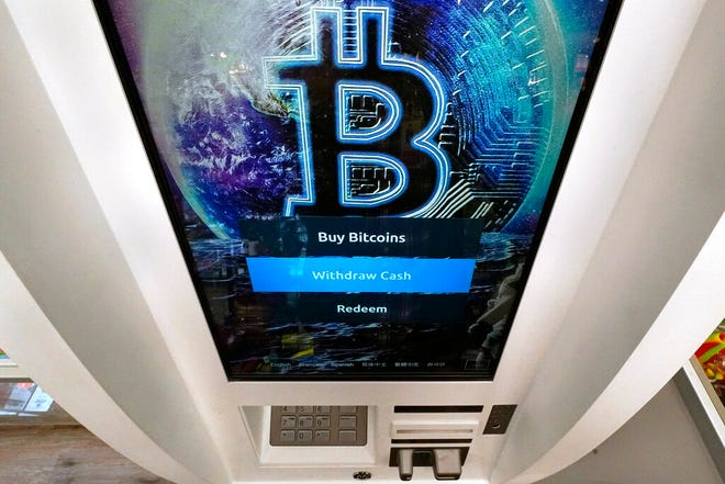 The Bitcoin logo appears on the display screen of a crypto currency ATM at the Smoker's Choice store, Tuesday, Feb. 9, 2021, in Salem, N.H.  After a wild week in which Bitcoin soared to new heights, Bitcoin is crossing the $50,000 mark. Bitcoin rallied last week as more companies signaled the volatile digital currency could eventually gain widespread acceptance as a means of payment for goods and services. (AP Photo/Charles Krupa)