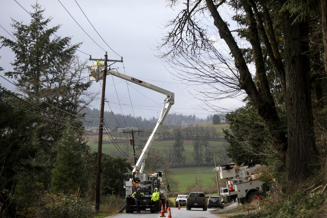 Crews work to restore power on Delaney Road SE south of Salem on Tuesday.