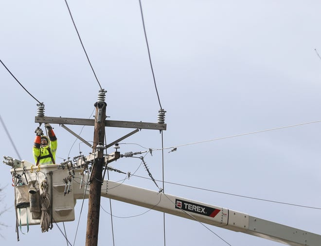Crews work to restore power on Delaney Road Southeast on Tuesday, Feb. 16, 2021 near Turner, Oregon.