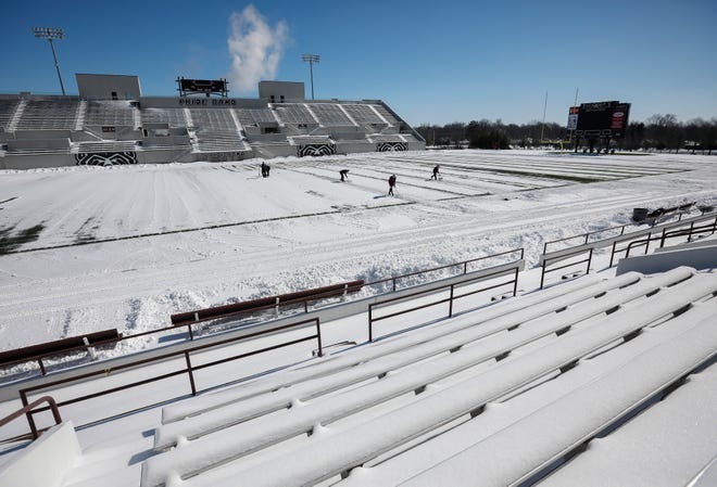 People shovel snow off of the yard markers on the football field at Plaster Stadium on Tuesday, Feb. 16, 2021.