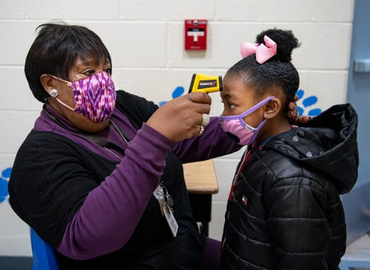Geraldine Robinson, a pre-kindergarten paraprofessional, takes the temperature of A'Toria Creer, a student on Feb. 1, 2021, at Parrish Elementary School in Carbondale, Ill.