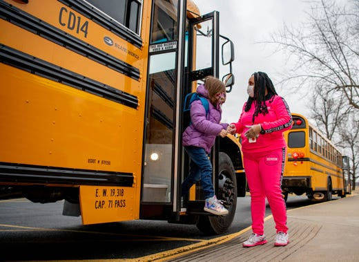 Olivia Jones-Martin, a pre-kindergarten instructional aid, helps students get off the bus on Feb. 1, 2021, at Parrish Elementary School in Carbondale, Ill. The school is taking various precautions, such as limited classroom sizes and social distancing, to prevent the spread of the novel coronavirus.