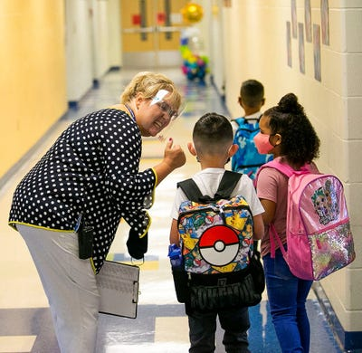 Marion Oaks Elementary School Principal Lisa Dreher gives a thumbs up to students as they arrive for the first day of school on Feb. 11, 2021. About 70% of the student body at Marion Oaks Elementary School in Ocala, Fla. decided to take part in face to face school during threat of COVID-19.