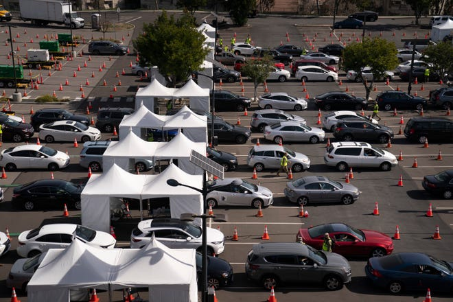 Motorists line up for their COVID-19 vaccine a joint state and federal mass vaccination site set up on the campus of California State University of Los Angeles in Los Angeles,Tuesday, Feb. 16, 2021.