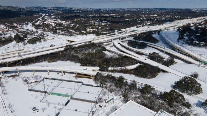 A few vehicles drive on Loop 1 (Mopac Boulevard) despite the snow on Feb. 15, 2021.