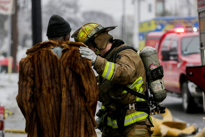 James Anyaegvu, who lived in an East Austin home that burned Wednesday, speaks with a firefighter on East 12th Street. Around noon, firefighters and emergency crews responded to a house fire that killed two people and left several injured.