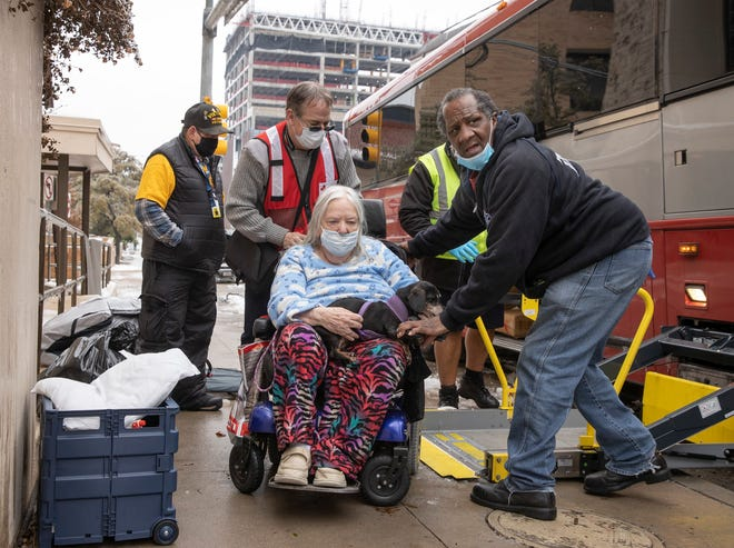 Dori Ann Upchurch is helped to a warming station at University Avenue Church of Christ on Wednesday February 17, 2021. She evacuated her home after she lost her water supply.