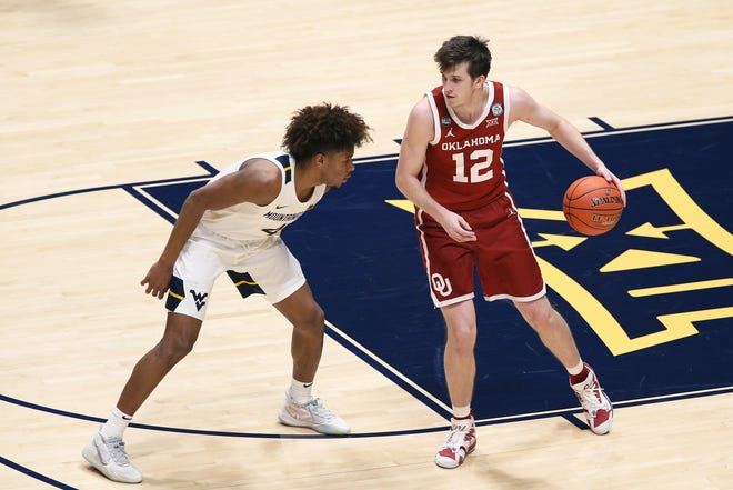 Oklahoma guard Austin Reaves (12) is defended by West Virginia guard Miles McBride (4) on Saturday, in Morgantown, W.Va. No. 9 Oklahoma's home game against No. 12 Texas has been canceled due to the ongoing winter weather slamming the region.