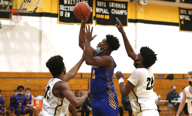 Lincoln Park's Montae Reddix (center) attempts a layup while being guarded by two Quaker Valley players during the second half Tuesday night at Quaker Valley High School.
