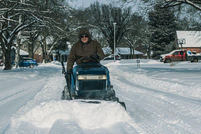 Tim Gardner does his part by plowing the roads in his neighborhood