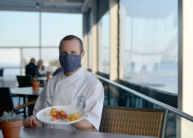 Executive chef Daniel Cote holds a plate of tuna crudo with Cape gooseberries, chips and cherry blossom soy sauce. Pelham House Resort offers rooftop dining with a view of Nantucket Sound.