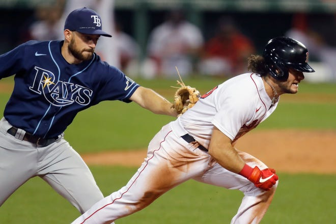 Tampa Bay Rays' Brandon Lowe tags Boston Red Sox's Andrew Benintendi on a rundown at third base during a game last season in Boston.