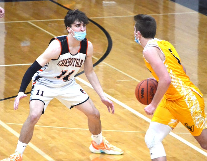 Junior David Heyer (left) at the Cheboygan varsity boys basketball team remained unbeaten in Straits Area Conference play after coming from behind to win at St. Ignace on Tuesday.