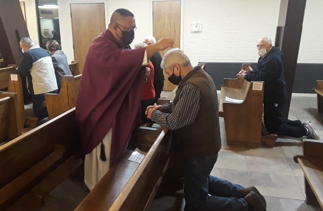 The Rev. Eric Leyble sprinkles ashes on parishioners' heads during Ash Wednesday morning services at St. Genevieve Catholic Church in Thibodaux. Due to virus restrictions, ashes weren't applied to the forehead.
