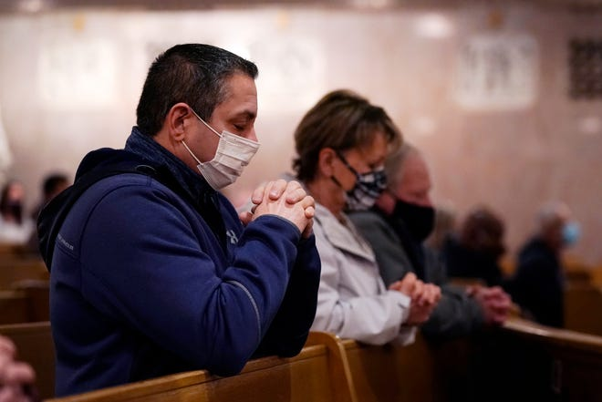 Bob Amore, foreground, and Denis Wood pray during Ash Wednesday service at the St. Aloysius Catholic Church, Wednesday, Feb. 17, 2021, in Detroit. The ashes, a symbol of penance, made from palm leaves used in last year's Palm Sunday liturgy were sprinkled on the forehead, because of the pandemic, which is a departure from the usual practice of making the sign of the cross on the forehead. The ritual follows an ancient method still common in parts of the world today.