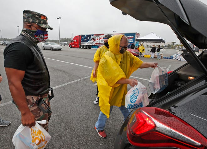 Volunteers load up cars with groceries and other items at One Daytona across from Daytona International Speedway on Wednesday, Feb 17, 2021. Convoy of Hope and NASCAR teamed up for the event to help those impacted by the economic fallout of the COVID-19 pandemic.