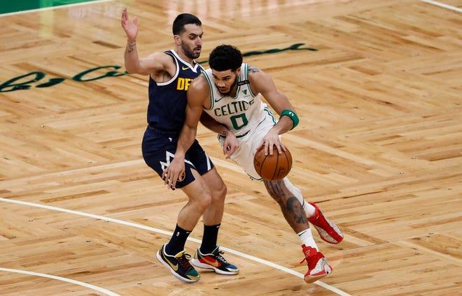 Feb 16, 2021; Boston, Massachusetts, USA; Boston Celtics forward Jayson Tatum (0) drives against Denver Nuggets guard Facundo Campazzo (left) during the first quarter at TD Garden.