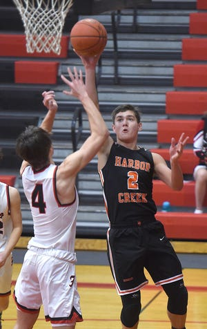 Harbor Creek's Casey Smith shoots over Fairview's Logan Frazao on Feb. 16, 2021 in the District 10 game at Fairview High School.