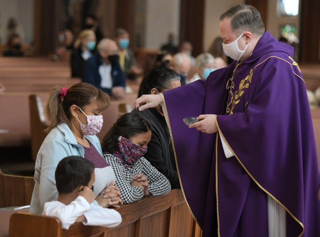 Ashes are sprinkled on on the head of Yaneryis Hall, 9, as she and her family attended Ash Wednesday services at San Jose Catholic Church in Jacksonville. The Vatican decreed that all U.S. priests, like the Rev. Remek Blaszkowski, do that instead of the traditional marking of a cross on foreheads due to the COVID-19 pandemic.