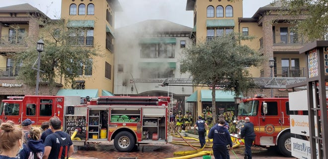Smoke pours from a second-floor apartment above an archway into a back parking lot next to the Tapestry Park Cafe.
