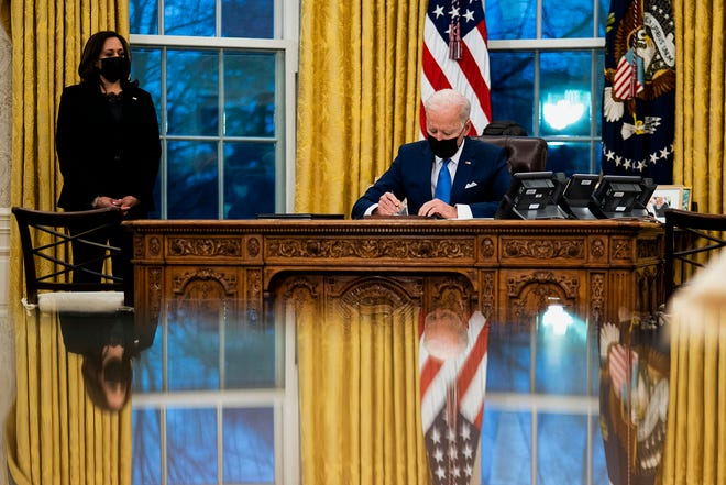 President Joe Biden signs several executive orders directing immigration actions for his administration as Vice President Kamala Harris looks on in the Oval Office at the White House in Washington, D.C., on Tuesday, Feb. 2, 2021.